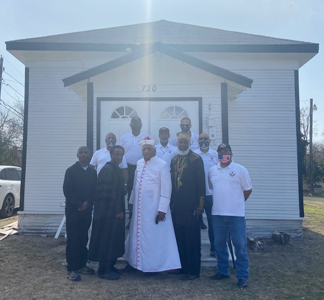 Church members and volunteers pose in front of the newly renovated church building.