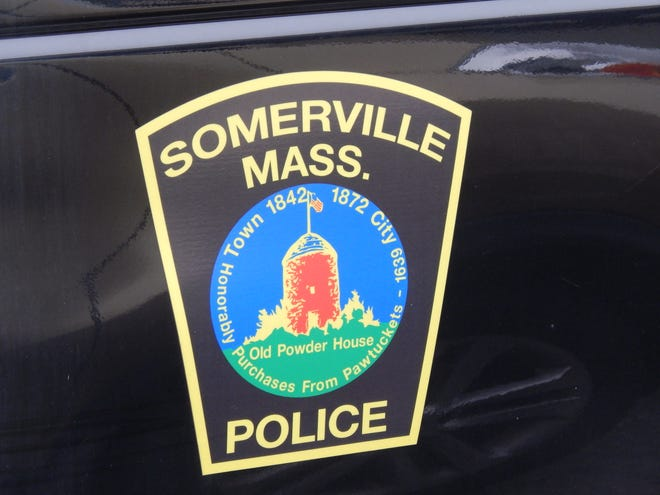 The Somerville Police seal on a police vehicle.