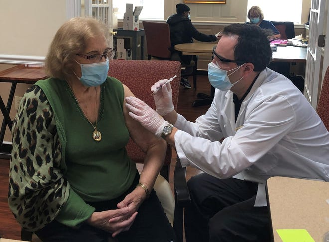 New Horizons resident Maria Alves receives a COVID-19 vaccination shot from a CVS team member.