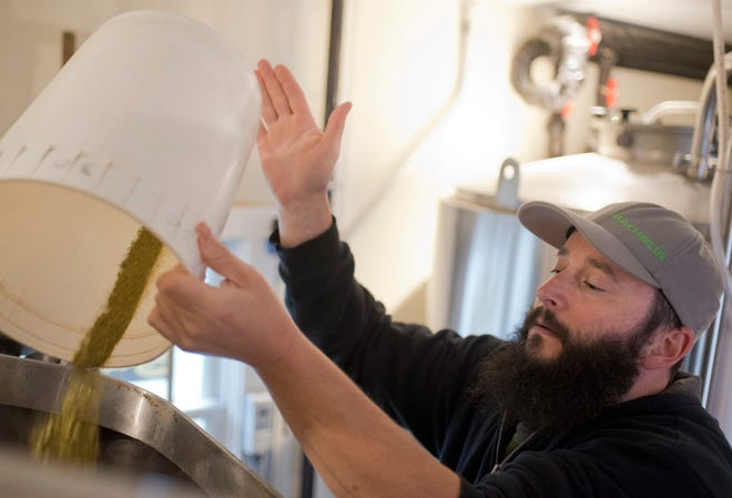 Flying Dreams brewmaster Dave Richardson shakes hops into the kettle while brewing the winter lager in 2017. Flying Dreams is no longer at the Park Avenue site in Worcester.