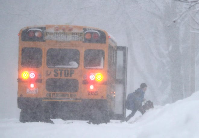 A school bus drops off a student as a snow storm moves across the state on Thursday, Feb. 4, 2021, in  Kaukauna, Wis.
