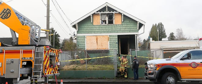 Bremerton firefighter/paramedic Kevin Bonsell lifts up the caution tape as he and fellow firefighter Elliott Wallace exit the scene of a house fire on Warren Ave. in Bremerton on Monday, Feb 8, 2021.