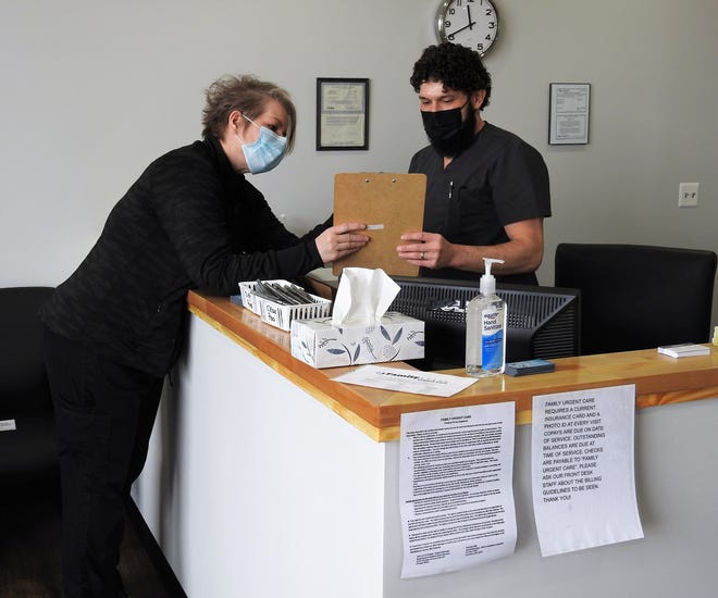 Nurse Practitioner Bonnie Austin reviews a clipboard with medical assistant Aaron Chaney at the new Family Urgent Care in Downtowner Plaza. The outlet is part of a chain of such facilities across Ohio under Dr.  Syed A. Naqvi.