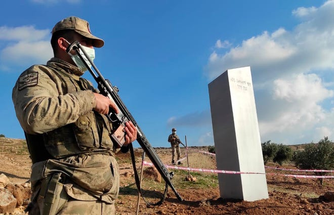 """Turkish police officers guard a monolith, found on an open field near Sanliurfa, southeastern Turkey, Sunday, Feb. 7, 2021. The metal block was found by a farmer Friday in Sanliurfa province with old Turkic script that reads """"Look at the sky, see the moon."""""""