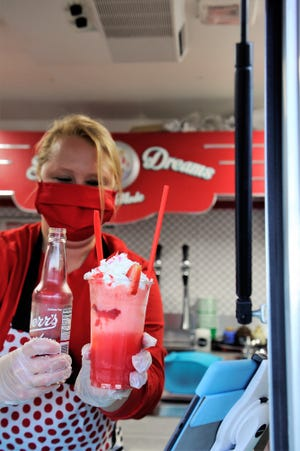 Angela Kissinger serves a Love Potion #9 float made with Derr's strawberry soda in the Sweet Dreams À La Mode truck on Friday, Feb. 5, 2021.