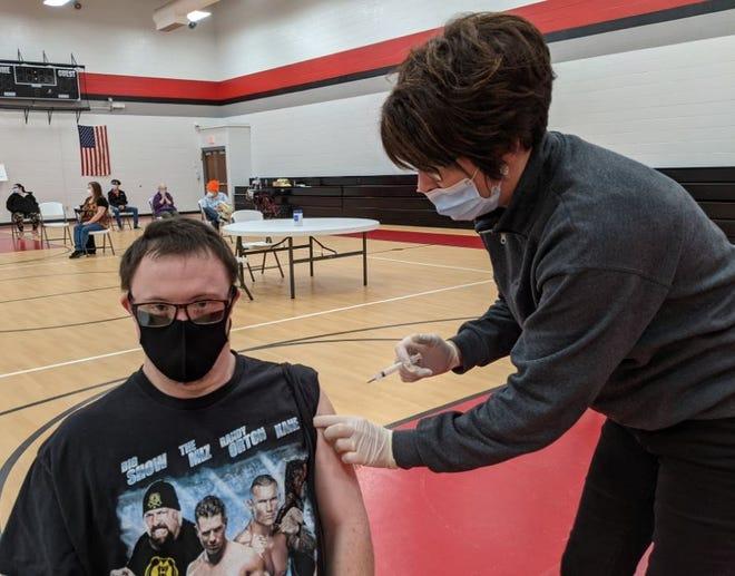 Adam McDermitt receives a Moderna COVID-19 vaccine from Trisha Reiter, a registered nurse at Sandusky County Public Health, at the Sandusky County Board of Developmental Disabilities on Monday.
