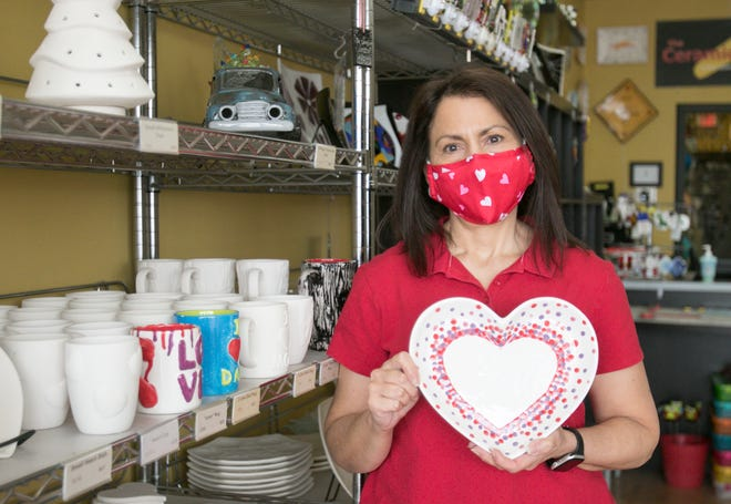 Helen Agius-Andreae, owner of The Ceramic Studio, Etc. displays a glazed ceramic heart in her Genoa Township shop Monday, Feb. 8, 2021, one of hundreds of pieces available to customers for Valentine's Day or any occasion.