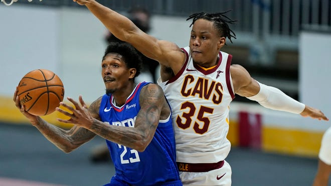 Los Angeles Clippers' Lou Williams (23) drives to the basket against Cleveland Cavaliers' Isaac Okoro (35) in the second half of an NBA basketball game, Wednesday, Feb. 3, 2021, in Cleveland. The Clippers won 121-99. (AP Photo/Tony Dejak).