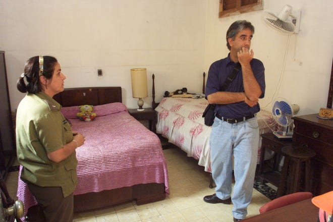 Vilma Varela-Alfonso, who lived in the home of Pedro Gomez's family in Cuba, shows Gomez the room where his grandparents slept.