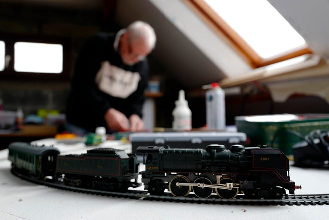 Guy Warein, a 70-year-old retiree, works on model trains in his home in Richebourg, northern France, Wednesday, Jan 27, 2021. The old-school pastimes of making scale models and playing with miniature trains are making a comeback as a form of therapy against the pandemic blues. Sales are booming as locked-down families glue and paint models and dust off train sets. (AP Photo/Michel Spingler)