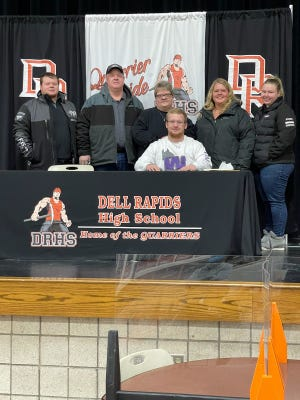 Zach Schreier (seated) signs to play football at Waldorf University during National Signing Day on Wednesday, Feb. 3, 2021.