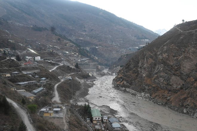 The remains of a dam (center) can be seen along a river in Tapovan in the Chamoli district of Uttarakhand, India, after a flash flood caused by a burst glacier on Feb. 7, 2021.