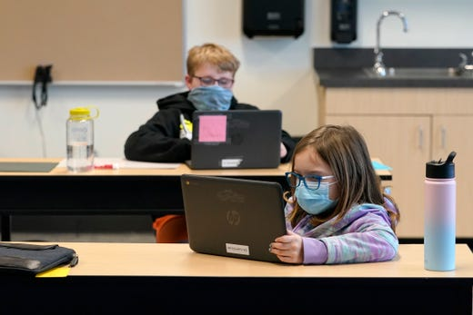 Students wear masks as they work in a fourth-grade classroom, Feb. 2, 2021, at Elk Ridge Elementary School in Buckley, Wash. The school has had some students in classrooms for in-person learning since September of 2020, but other students who attend the school are still learning remotely.
