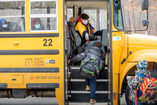 Rycc Smith welcomes Montello Elementary School students as they board his bus outside the Lewiston, Maine school, Jan. 21, 2021 after the first day back in nearly a month. The entire school district switched to all remote learning after an uptick in COVID-19 cases last month. Smith has been driving a school bus for the past 40 years and said the students have been very cooperative following the protocols.
