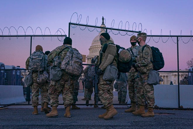 National Guard members enter barbed wire gate to protect the Capitol on Feb. 8, 2021, in Washington, D.C.