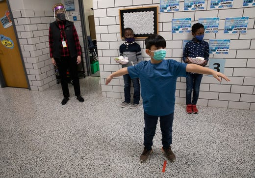 Second grader Cody Yang spreads out his arms as he practices socially distancing while standing in the hallway Jan. 19, 2021 at Park Brook Elementary School in Brooklyn Park, Minn. About 100 students in prekindergarten to second grade returned to school for in-person learning.