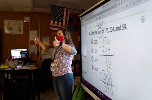 Full-time 3rd grade teacher Kathryn Dorros gives her students a thumbs up after they answered her questions correctly at Grassy Waters Elementary School in West Palm Beach, Fla. on Jan. 8, 2021.