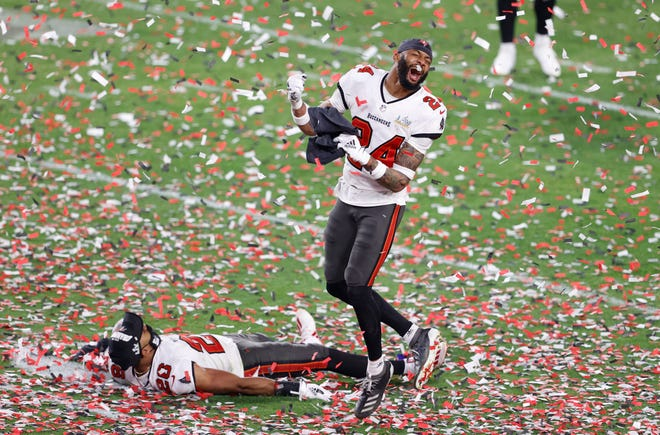 Tampa Bay Buccaneers cornerback Carlton Davis (24) and defensive back Andrew Adams (26) celebrate after defeating the Kansas City Chiefs in Super Bowl 55 at Raymond James Stadium.