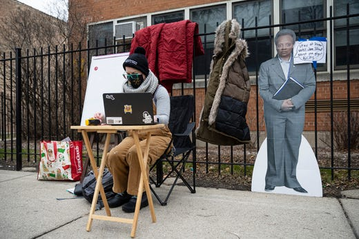 A teacher sets up her laptop outside of Suder Montessori Magnet Elementary School to begin virtual classes in solidarity with pre-K educators forced back into the building in Chicago, Jan. 11, 2021.