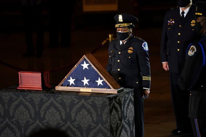 Acting U.S. Capitol Police Chief Yogananda Pittman pays respects to U.S. Capitol Police officer Brian Sicknick as an urn with his cremated remains lies in honor on a black-draped table at center of Capitol Rotunda, Tuesday, Feb. 2, 2021, in Washington. (Erin Schaff/The New York Times via AP, Pool) ORG XMIT: NYNYT413