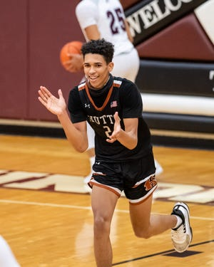 Jailen Bedford celebrates after his basket put Hutto ahead late in the game. Hutto won a district boys basketball game at Round Rock 63-59 on Feb. 8.
