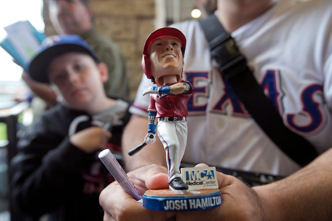 A Round Rock Express fan holds a bobblehead of Texas Rangers outfielder Josh Hamilton before a 2015 Express game. On Tuesday, the Triple-A club formally announced a 10-year affiliation with the Rangers after just one year as a minor league club of the Houston Astros.
