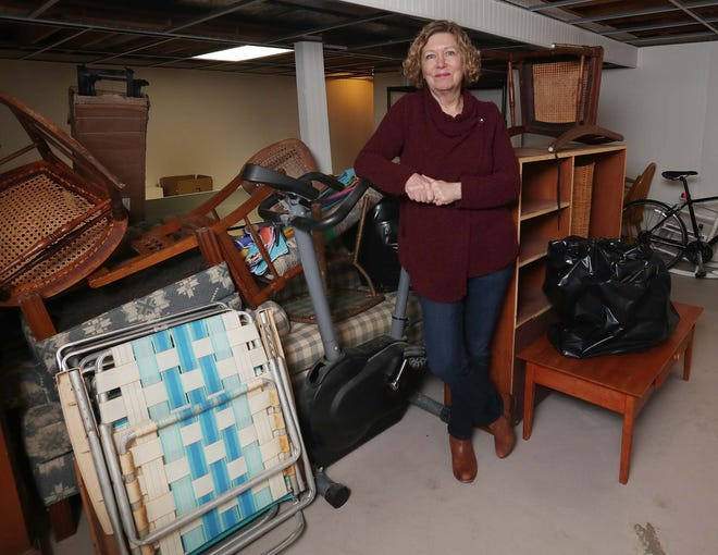 Mary Beth Breckenridge with items that have been deemed unsalvageable after a smoldering fire in the ash collection pit under the fireplace this winter caused smoke damage in her home in Brecksville.