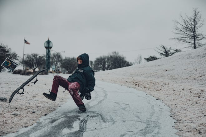 Caleb Conditt takes a spill while snowboarding on the ice at Sooner Park in Bartlesville.