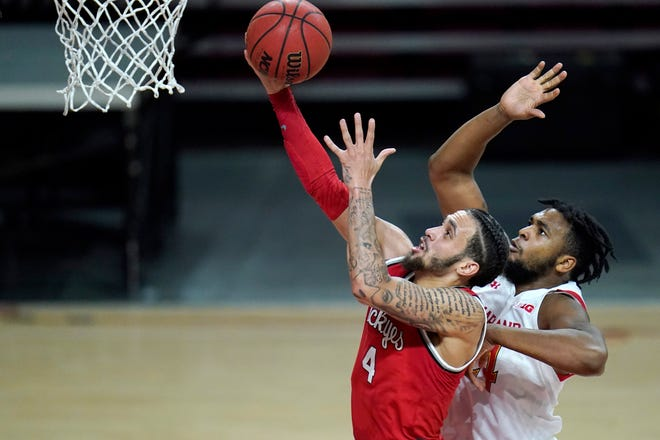 Ohio State guard Duane Washington Jr., left, goes up for a shot against Maryland forward Donta Scott during the second half of an NCAA college basketball game, Monday, Feb. 8, 2021, in College Park, Md. Ohio State won 73-65.
