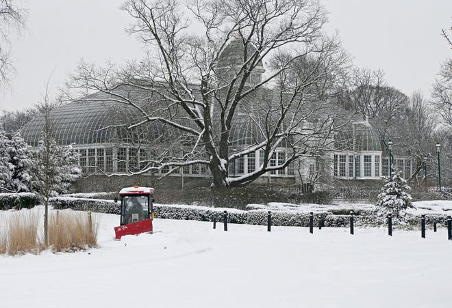 A worker clears a path on the west side of the Franklin Park Conservatory with the John F. Wolfe Palm House in the background on Tuesday after several more inches of fresh snow fell on Columbus overnight. More is on the way Wednesday.