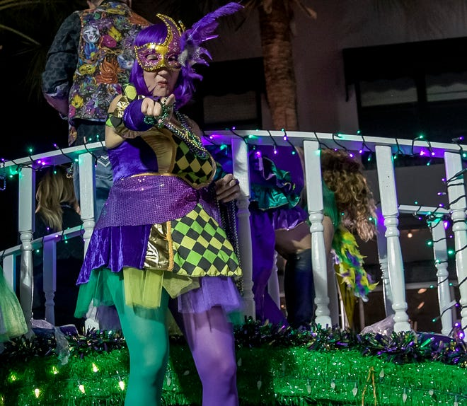 A woman gestures from a float during the 2020 Leesburg Mardi Gras parade in downtown Leesburg.