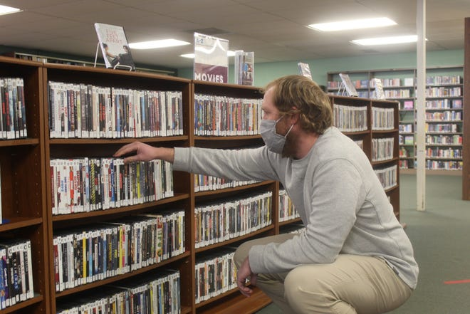 Trevor Van Valkenburg, director of the Lenawee District Library, checks the DVD shelves on Monday. With Family Video set to close, libraries are one of the last remaining places to rent a hard copy movie.