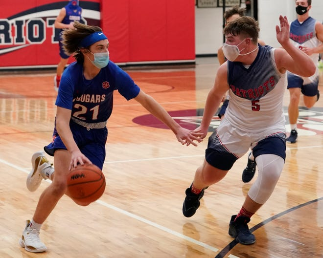 Lenawee Christian's Tyler VanEtten handles the ball while defended by Britton Deerfield's Logan Shiels during Monday's game. Mike Dickie