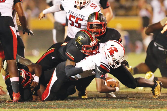 Salisbury's Jadirus Woods, Zae Clay and Jabril Norman combine to bring down Central Davidson's Cory Casilac in the backfield in a 2019 game. The Spartans began to practice officially on Monday. [James Sipes for the Salisbury Post]