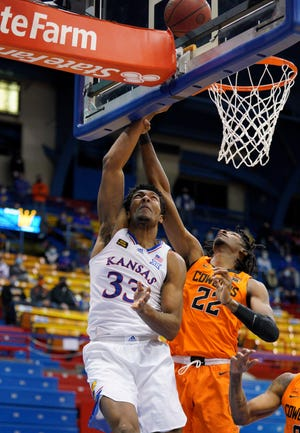 Kansas forward David McCormack (33) shoots over Oklahoma State forward Kalib Boone (22) during the first half of Monday's game at Allen Fieldhouse. McCormack tallied 23 points – 21 in the second half – and 10 rebounds to lead the Jayhawks to a 78-66 win over the No. 23 Cowboys.