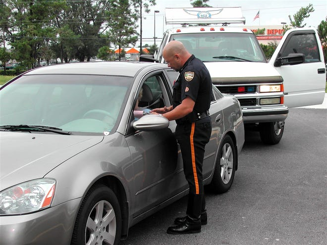 A Jacksonville traffic enforcement officer gives a ticket for running a red light to a driver at  Atlantic and Kernan boulevards in this Times-Union file photo. Drivers who have overdue tickets can take advantage of Operation Green Light to pay them off without the collections surcharge and potentially get their licenses reinstated.