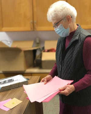 "Carolina Village resident Kay Williams stocks up on supplies for her valentine creations and stops to read Activity Coordinator Jessica Wright's creation, ""Bee My Valentine,"" featuring a thumbprint bee."