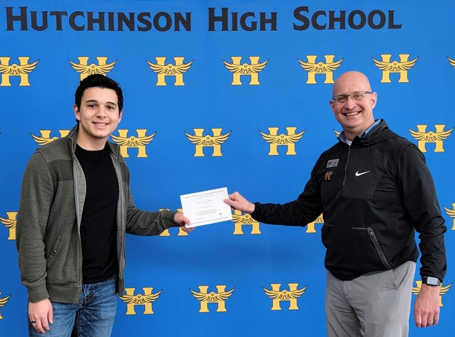 William Jackson receives his National Merit finalist certificate from HHS Principal Ryan Ewy.