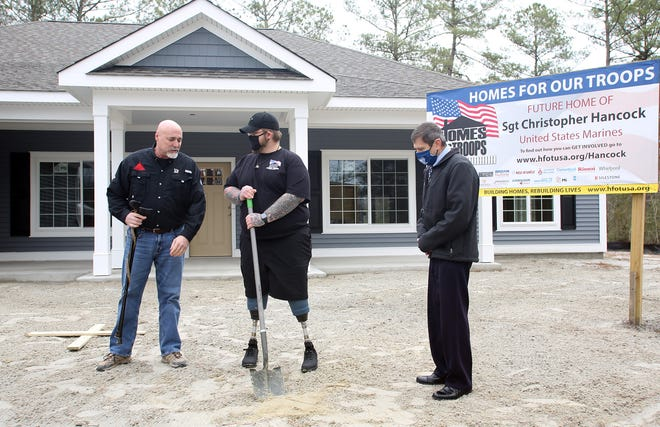 Doug Downing (left), Channel Marker Builders, LLC.,  and Bill Ivey, Homes For Our Troops, executive director, (right) look on as Christopher Hancock speaks to attendees at his groundbreaking home dedication.  [John Althouse / The Daily News]