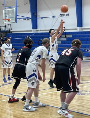 Brian Aguilar shoots a free throw against Hoehne while Kaden Maes and Caden Morlan look on.