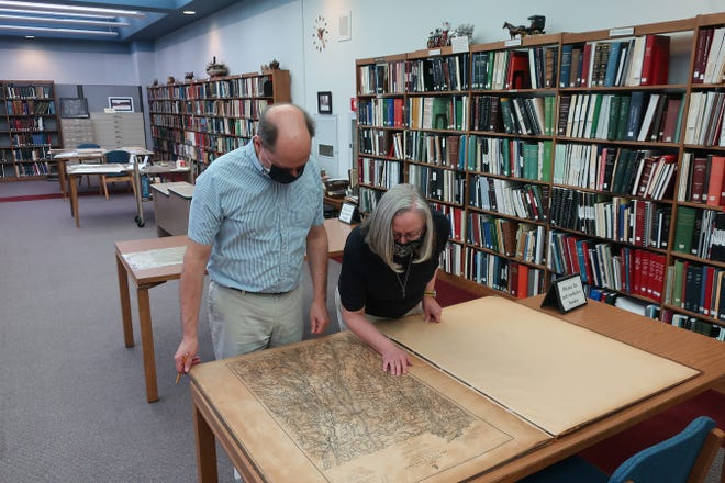 John Ransom and Pat Breno – Head Librarian John Ransom, (left), and Librarian Pat Breno examine a book of historic maps of Civil War battles. This book is part of the map collections at the Hayes Presidential Library & Museums. [Courtesy photo]