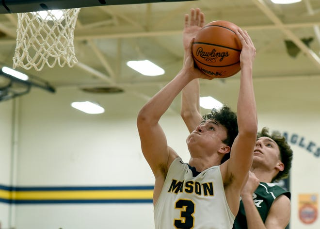 Tanner Herrera of Mason drives to the hoop as Timothy Barno of SMCC  attempts to block at the district semifinals at Mason Wednesday. [MONROE NEWS PHOTO BY TOM HAWLEY]