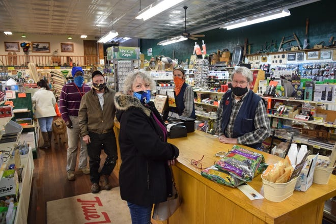 Ron McCloud, proprietor of Dunsmuir Hardware, helps Kelley Brentt as employee Kevin Tynsky waits on customers Doyle Roate and Curtis Smith on the first day the store re-opened on Feb. 8. 2021. The store was closed for more than two months after McCloud contracted COVID-19.