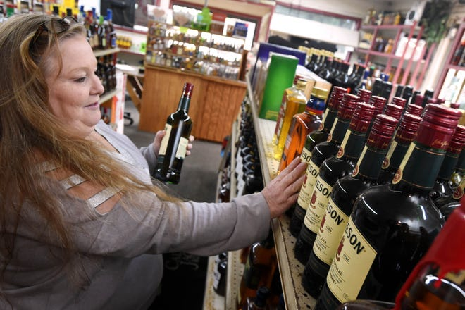 Joyce Dunham stocks liquor at Cash's Icehouse in Crestview. The City Council on Monday voted to allow alcohol sales to begin at 7 a.m. on Sundays, but Icehouse owner Cash Moore said he will continue to open his store at 1 p.m.