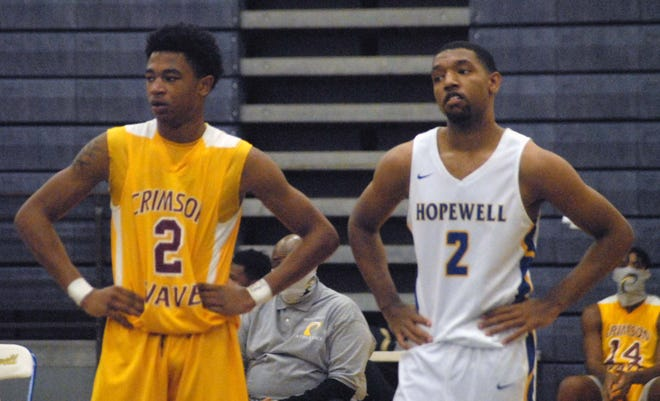 Petersburg's Tylik Lawrence (in yellow on left) stands with Hopewell's Elvin Edmonds (in white on right) during Hopewell's 79-67 win on January 8.