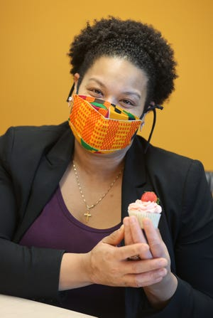 Marissa Mathews, owner of Busy B Bakery, shows off one of her strawberry champagne cupcakes.