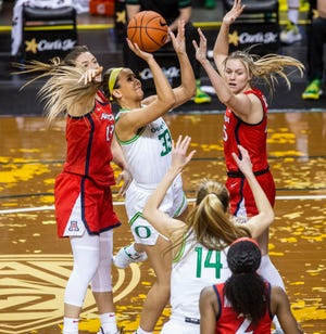 Oregon's Sydney Parrish (33) shoots against the defense of Arizona's Cate Reese, left, and Helena Pueyo during Monday's game at Matthew Knight Arena.