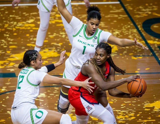 Oregon's Te-Hina Paopao (12) and Nyara Sabally (0) defend Arizona's Trinity Baptiste during a Feb. 8 game against the Wildcats at Matthew Knight Arena.