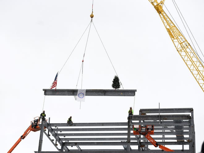 Members of Iron Workers Local 550, based in Canton and working with Kelley Steel Erectors from Cleveland, hoist the last steel beam into place at the Constellation Center for Excellence on the campus of the Hall of Fame Village powered by Johnson Controls. The 75,000-square-foot office building anchors the west end of Tom Benson Hall of Fame Stadium.
