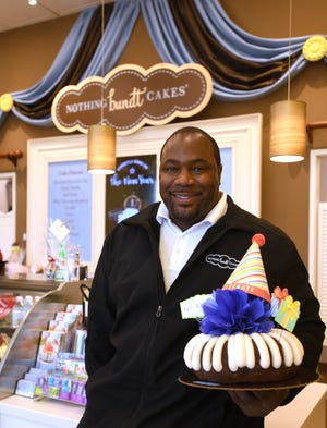 Nothing Bundt Cakes owner Kenny Peterson poses with a cake